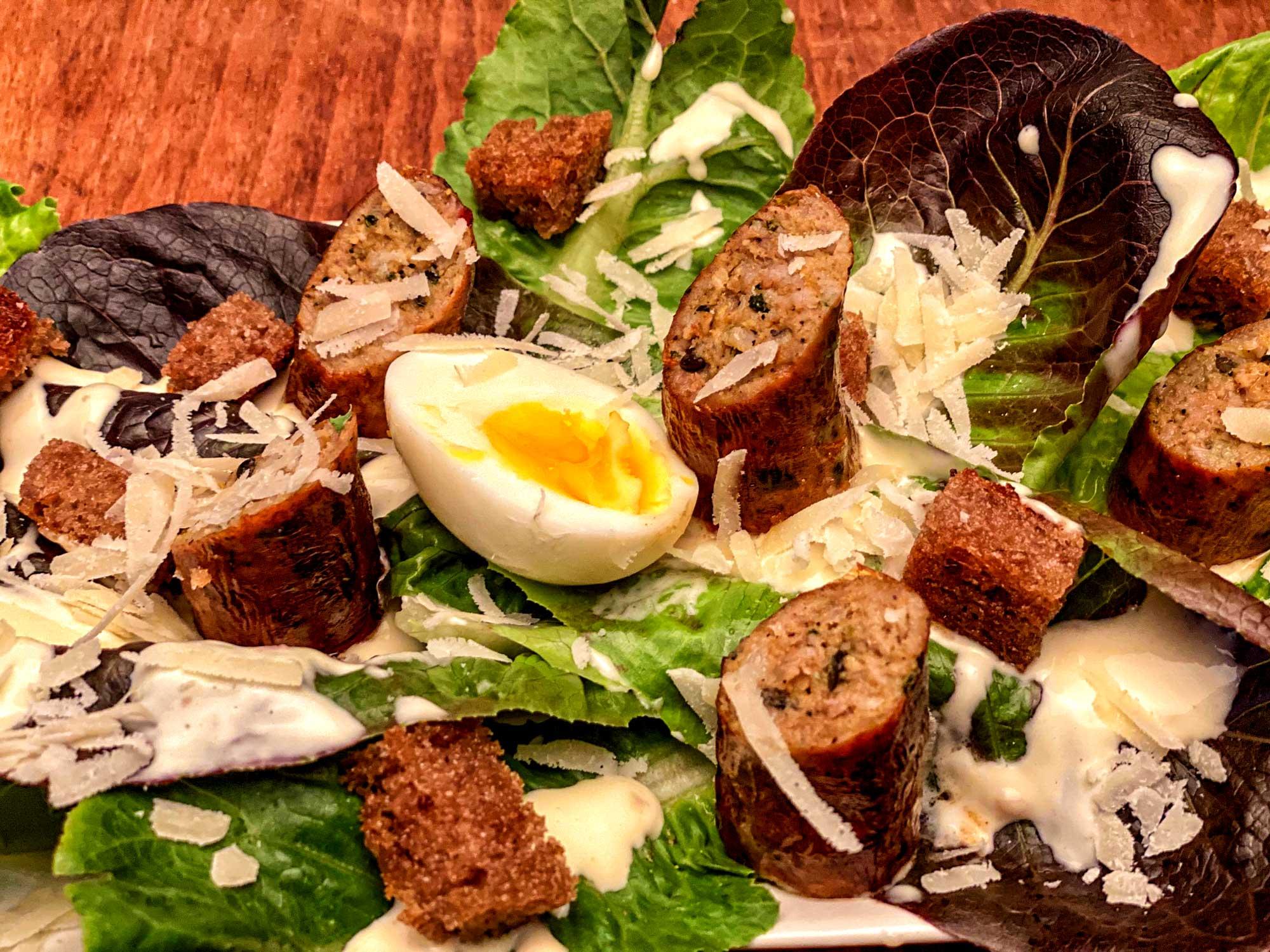 Die Surf and Turf Bratwurst aus der Metzgerei Kirchschlager in Erbach auf einem Caesar Salad.